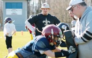 Sporting a New Orleans Saints shirt and BC Lions hat, Adam Bighill oversees a drill during the Bulldogs' spring camp at McAdam Park. (Kevin Rothbauer/Citizen)